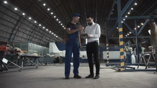 Mechanic and flight engineer having a discussion together as they stand in aircraft in a hangar