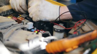 Mechanic checks electric components in hood of the car - automobile service diagnostics