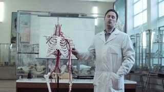 Medical professor in anatomy class with skeleton panning out to see students