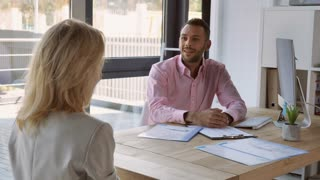 Meeting in employment agency office. Unrecognizable woman have an interview with mixed race cheerful man. People sitting at the desk talking with friendly smile. Businessman shaking hand blond female