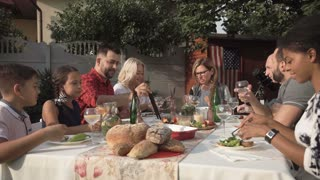 Middle angle of cheerful big American family sitting and eating in the garden during reunion party
