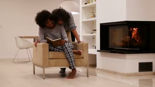 mixed race couple reading book beside fireplace in modern apartment
