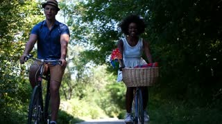 mixed race couple riding bike in park
