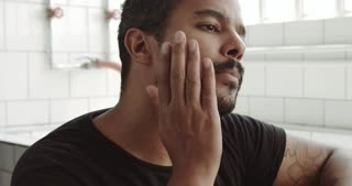 mixed race man touches his face and beard before shaving
