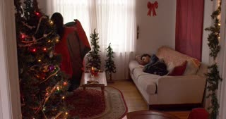 Mom puts blanket on sleepy son on Christmas morning. They all exchange gifts. Slow motion.