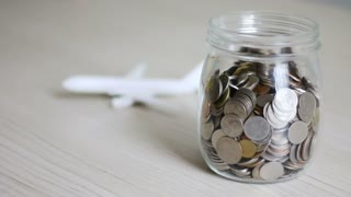 Money Coin Falling Into Glass Jar And Blur Air Plane Behind Metaphor Of Saving Money For Travel And Transportation Concept