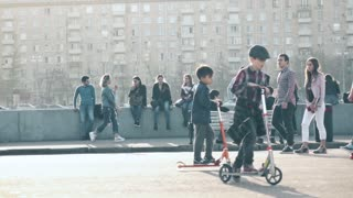 MOSCOW, RUSSIA - APRIL, 29, 2017. Slow motion video of young people skateboarding and riding scooters