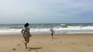 Mother And Child Running At The Beach Together