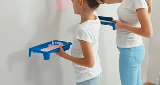 Mother And Daughter Painting On The Wall Together