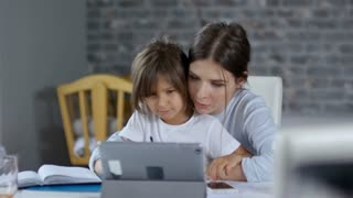 Mother using tablet computer for remote video communication and helping her daughter with homework, her son is busy in the background