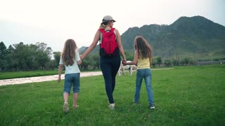mother walking with daughters in the meadow with grazing horses. happy family travels. slow motion