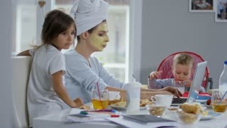 Mother with face mask and towel on her head working online on laptop computer and having breakfast with two children who are disturbing her
