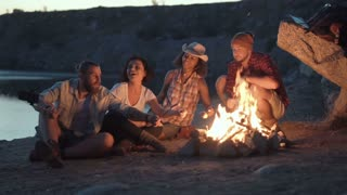 Movement stabilized slow motion shot of group of multiracial people sitting around campfire grilling marshmallows and having fun on coast on lake