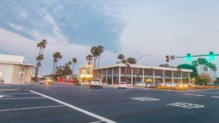Moving timelapse in motion (hyperlapse) shot at sunset facing busy Lido intersection with traffic and palm trees in Newport Beach. Shot at twilight with the sky changing from day to night with stunning moonrise and clouds above.