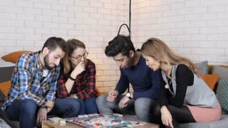 Multinational company sit on the couch and play monopoly board game 50 fps