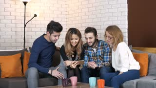 Multinational company sit on the couch and watch interesting videos on smartphone 50 fps