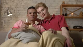 Multinational gay couple sitting on couch covered with a warm blanket, look at the camera. Homeliness, romantic evening, background, hugs, happy LGBT family concept. 60 fps