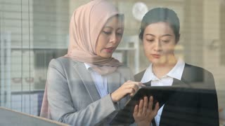 Muslim and Asian businesswomen discussing important office details