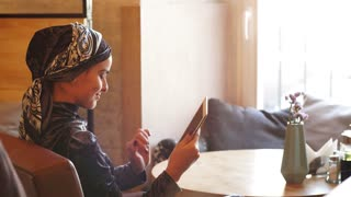 Muslim Business Woman Working on Tablet in Cafe