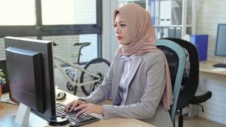Muslim businesswoman working on her laptop