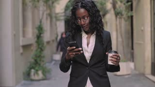 Natural afro american beauty business woman in stylish outfit for office work, walks on street with take away coffee cup,looks at screen of smartphone,checks emails and notifications from applications