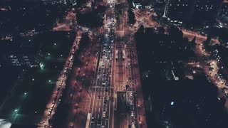 Night time commuter traffic with cars and business offices, aerial drone footage flyover of impressive big city life with lights and road junctions on highway urban city planning