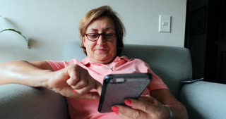 Older Woman Seated On Sofa Holding Cellphone Device Candid 4 K Clip Of Elder Woman Using Phone To Browse The Internet 2