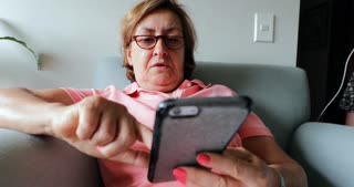 Older Woman Seated On Sofa Holding Cellphone Device Candid 4 K Clip Of Elder Woman Using Phone To Browse The Internet