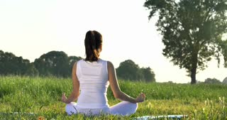 On a sunny day, a beautiful young girl does yoga in nature (park, field), in white clothes in the background of grass, wood, sky. Concept: ecology, clean air, summer, spring, qi energy, harmony.