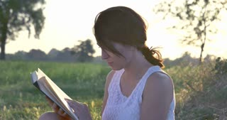 On a sunny day, a beautiful young student girl reads a book in nature (in a park, on a field) against a background of grass and sky. Concept ecology, clean air, summer, spring, grass, study, education