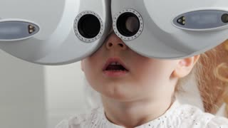 Ophthalmology clinic - adorable little blonde girl checks vision eyesight, close up