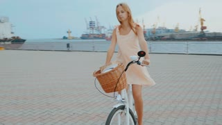 Outdoor fashion portrait of elegant blonde lady riding her hipster retro bike in vintage stylish dress. Enjoy summer day,posing at the marine port. Casual lifestyle. Slow motion