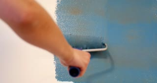 Painting wall and renovating apartment, close up of hand with roller painting wall