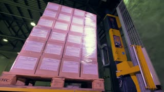 Pallet of boxes wrapping by a industrial machine. 4K.