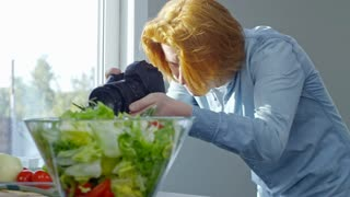 PAN with tilt up of professional cook squeezing lemon juice into clear bowl while preparing salad dressing and talking as young man recording on digital camera