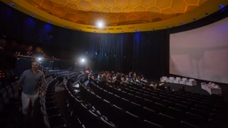 Panning Time Lapse of Audience Filling Movie Theater for Screening