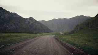 Panorama of mountains and a dirt road in the field