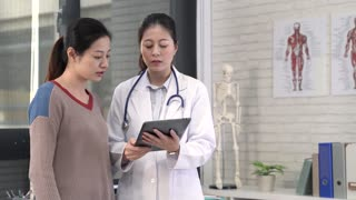 Asian doctor and patient stand side by side to discuss diagnosis