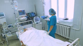 Patient in a hospital room connected to medical equipment.