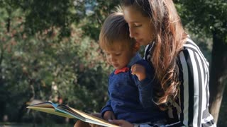 People and education, mother and her child sitting on grass and reading book at park. Young beautiful woman with son enjoy nature. Slow motion