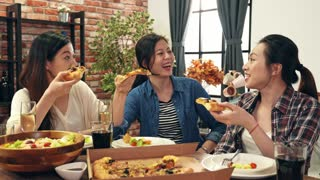 Asian women friends enjoying life and eating pizza
