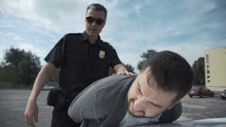 Police officer arresting criminal, putting him on car trunk and reading rights for him