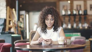 Portrait of a beautiful hispanic girl in a cafe. girl texting message on smartphone and smiles