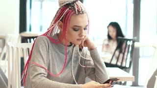 portrait of a girl with dreadlocks in a cafe. a teenager with an unusual appearance. subculture of modern youth