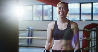 Portrait of a professional boxer girl in a sports hall, after coaching smiling and having fun, wearing black gloves, excellent body and preparation. Concept: love of sport, young boxers, love to win.