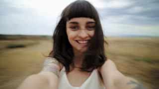 Portrait of attractive natural happy young brunette female spins around in middle of field during advneture vacation journey through national park, concept freedom, youth, integrity, eco consciousness