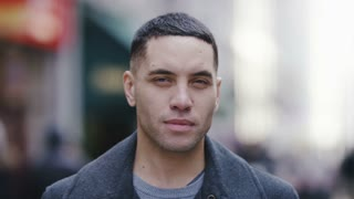 Portrait of handsome mixed race male smiling to camera in a busy high street, in slow motion