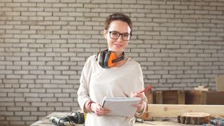 Portrait of happy attractive hardworking professional female worker with pen and tablet in workshop