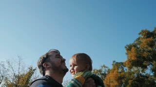 Portrait of happy young father and his son in autumn park. Slow motion. Playing with baby boy outdoor. Handsome man throwing his adorable child in the air