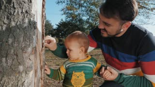 Portrait of happy young father and his son in autumn park. Slow motion. Playing with baby boy outdoor. Man shows tree to child, introduces nature to him